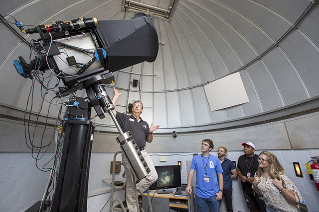 Professor showing students astronomy telescope