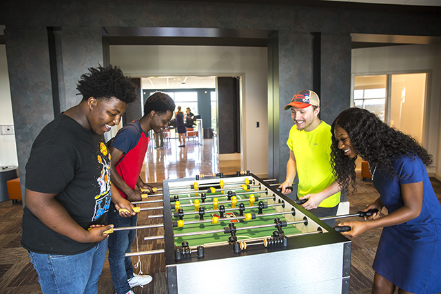 Four students playing foosball